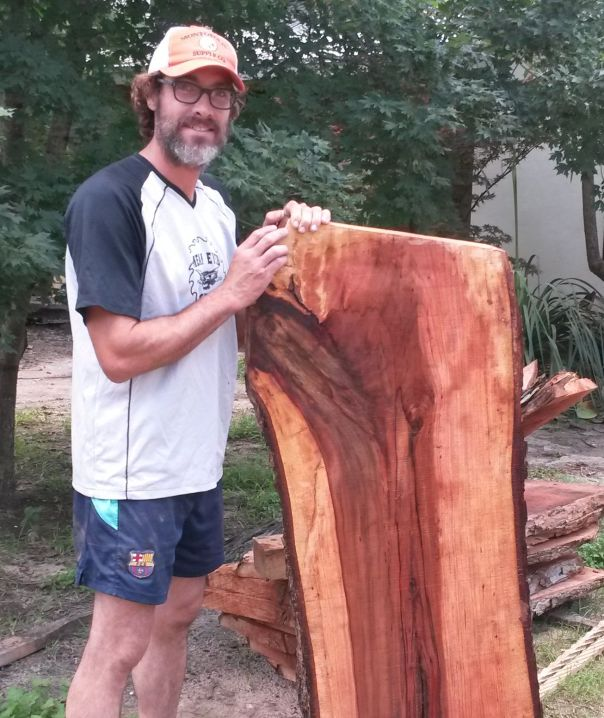 Daniel Baugh holding a slab of pecan that could one day be a fine piece of beautiful furniture.